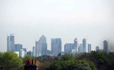 FILE PHOTO: The Canary Wharf financial district is seen above a residential rooftop in London
