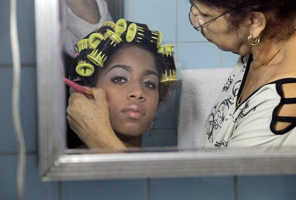 <p>Carmen Gonzalez (L) has make-up applied as she prepares for her quinceanera.</p>