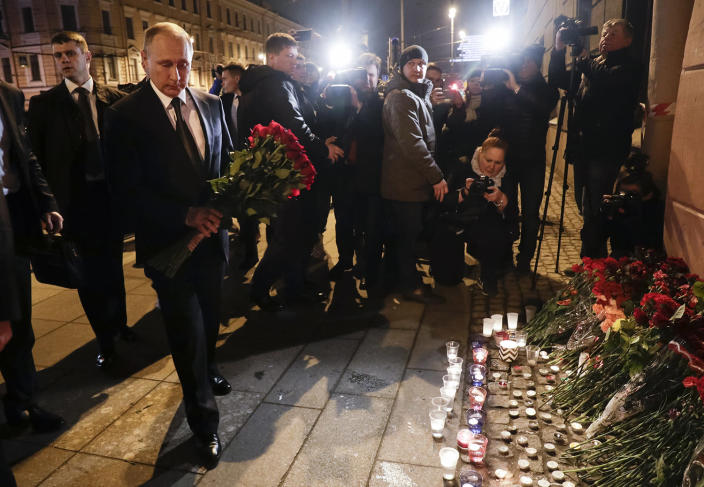 <p>Russian President Vladimir Putin, second left, lays flowers at a place near the Tekhnologichesky Institut subway station in St.Petersburg, Russia, Monday, April 3, 2017. A bomb blast tore through a subway train deep under Russia's second-largest city Monday, killing several people and wounding many more in a chaotic scene that left victims sprawled on a smoky platform. (Dmitri Lovetsky/AP) </p>