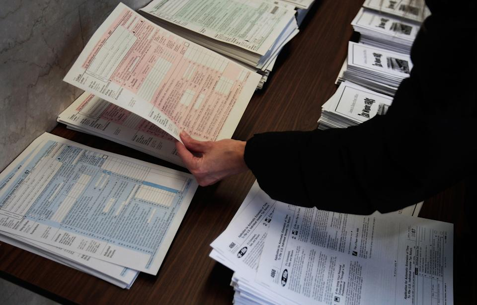 A woman picks up tax forms in the lobby of the Farley Post Office in New York City. (Photo: Chris Hondros/Getty Images)