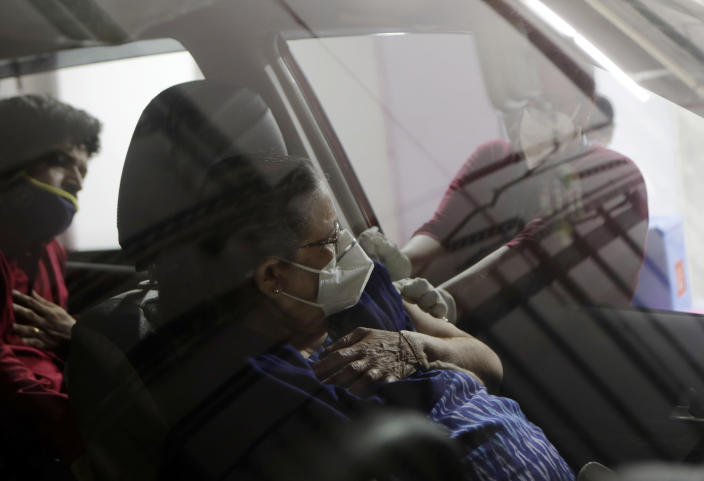 A woman receives a vaccine for COVID-19 in her car at a drive-in vaccination centre in Mumbai, India, Tuesday, May 4, 2021. COVID-19 infections and deaths are mounting with alarming speed in India with no end in sight to the crisis. (AP Photo/Rajanish Kakade)