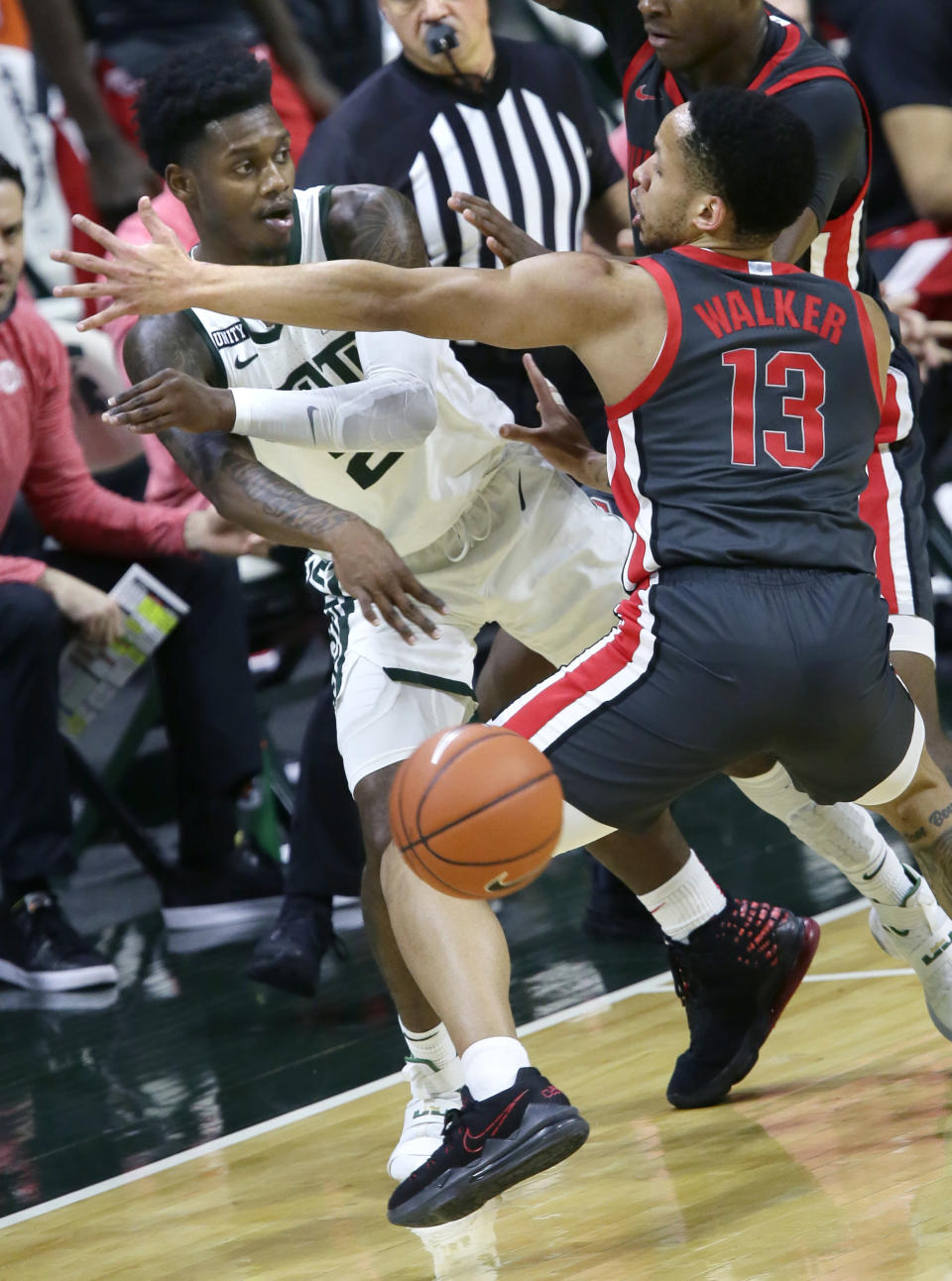 Michigan State guard Rocket Watts (2) passes the ball past Ohio State guard CJ Walker (13) during the first half of an NCAA college basketball game Thursday, Feb. 25, 2021, in East Lansing, Mich. (AP Photo/Duane Burleson)