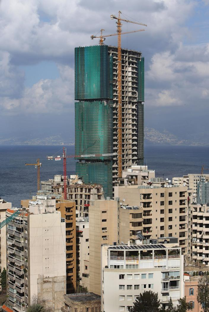 In this February 18, 2014 photo, a luxury tower, center, is under construction on the seafront, in Beirut, Lebanon. A famously scenic Mediterranean city surrounded by once lush mountains, Beirut may soon be overrun with buildings -- all at the expense of green parks and pedestrian areas. While Lebanon's real estate sector has developed to become one of the country's success stories, many say it is coming at the expense of Lebanon's identity and heritage.(AP Photo/Hussein Malla)