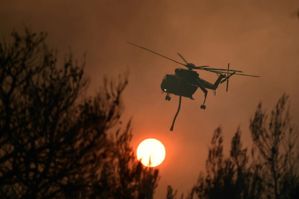 An helicopter operates during a wildfire in Kryoneri area, northern Athens, Greece, Thursday, Aug. 5, 2021. Wildfires rekindled outside Athens and forced more evacuations around southern Greece Thursday as weather conditions worsened and firefighters in a round-the-clock battle stopped the flames just outside the birthplace of the ancient Olympics. (AP Photo/Michael Varaklas)