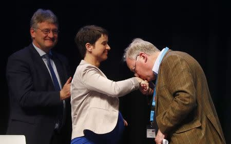 Alexander Gauland of Germany's anti-immigration party Alternative for Germany (AFD) kisses the hand of party chairwoman Frauke Petry as Joerg Meuthen looks on during an AFD party congress in Cologne Germany, April 23, 2017. REUTERS/Wolfgang Rattay