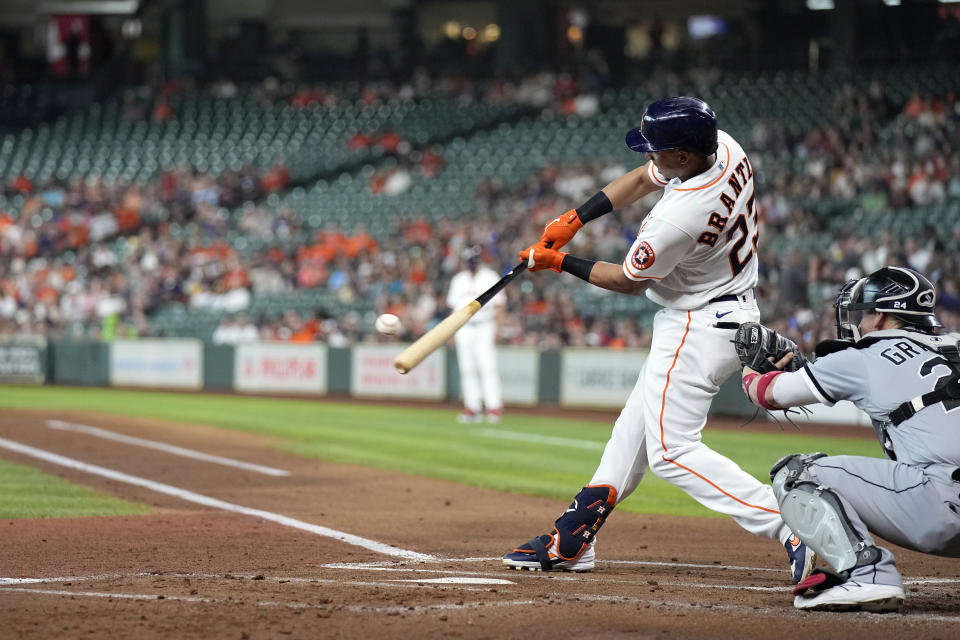 Houston Astros' Michael Brantley (23) hits a three-run home run as Chicago White Sox catcher Yasmani Grandal reaches for the pitch during the first inning of a baseball game Thursday, June 17, 2021, in Houston. (AP Photo/David J. Phillip)
