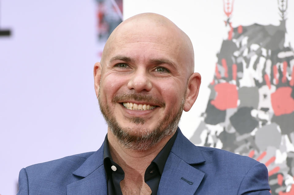 """FILE - Pitbull smiles during a hand and footprint ceremony at the TCL Chinese Theatre in Los Angeles, in this Friday, Dec. 14, 2018, file photo. NASCAR is being heavily promoted by a broadcast partner as about to embark on """"The Best Season Ever"""" and on paper that could be true. NASCAR this year will race on dirt for the first time since 1970, the schedule includes a whopping seven road courses and five venues new to the Cup Series. Michael Jordan and Pitbull are among new team owners entering the sport in 2021 and Chase Elliott, NASCAR's most popular driver, is the reigning champion. (Photo by Chris Pizzello/Invision/AP, File)"""