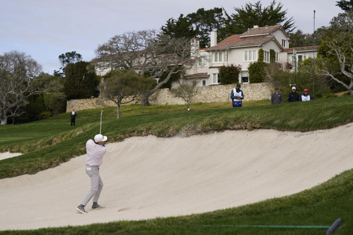 Nate Lashley hits out of a bunker up to the first green of the Pebble Beach Golf Links during the final round of the AT&T Pebble Beach Pro-Am golf tournament Sunday, Feb. 14, 2021, in Pebble Beach, Calif. Jordan Spieth, third from right, and Tom Hoge, second from right, look on. (AP Photo/Eric Risberg)