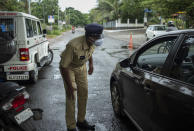 A policeman bends down to check the occupants of a car as he enforces a weekend lockdown to curb the spread of COVID-19 in Kochi, Kerala state, India, Sunday, Aug.29, 2021. (AP Photo/R S Iyer)