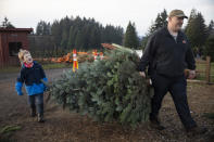 Tim Daley and son Jacob, 9 years, from Tualatin carry their freshly cut Christmas tree at Lee farms on Saturday, Nov. 21, 2020 in Tualatin, Ore. It's early in the season, but both wholesale tree farmers and small cut-your-own lots are reporting strong demand, with many opening well before Thanksgiving. (AP Photo/Paula Bronstein)