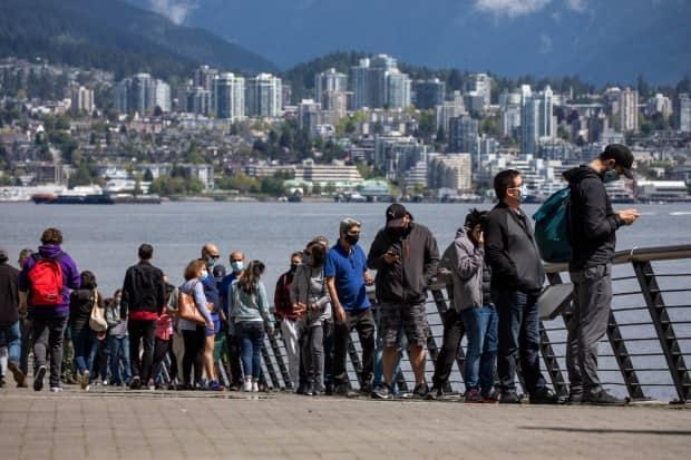 Essential workers which include restaurant staff are pictured in a lineup outside the Vancouver Convention Centre during a COVID-19 vaccination clinic in Vancouver, British Columbia on Friday, May 7, 2021.  (Ben Nelms/CBC - image credit)