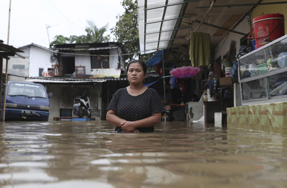 A woman pauses as she stands in flood water at a flooded neighborhood in Jakarta, Indonesia, Tuesday, Feb. 25, 2020. Overnight rains caused rivers to burst their banks in greater Jakarta sending muddy water into residential and commercial areas, inundating thousands of homes and paralyzing parts of the city's transport networks, officials said. (AP Photo/Achmad Ibrahim)