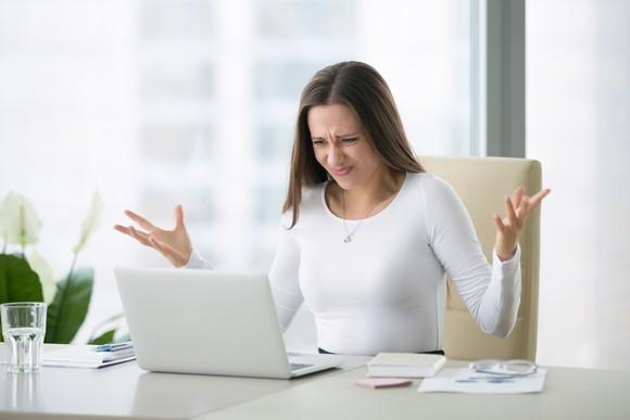 A woman raises her hands in exasperation while sitting in front of a laptop.