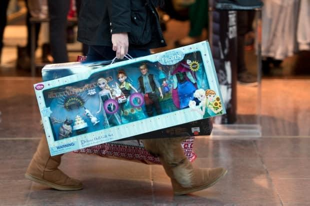 Disney announced in March that it planned to close 60 locations across North America this year, but had no specific comment on its Canadian locations. Now it appears as though all Canadian locations will be closed by next month. In this picture, a shopper carries Disney's Frozen dolls sets as she walks through the Trafford Centre shopping mall past retailers offering Black Friday discounts in Manchester, northern England on Nov. 27, 2015.  ( - image credit)