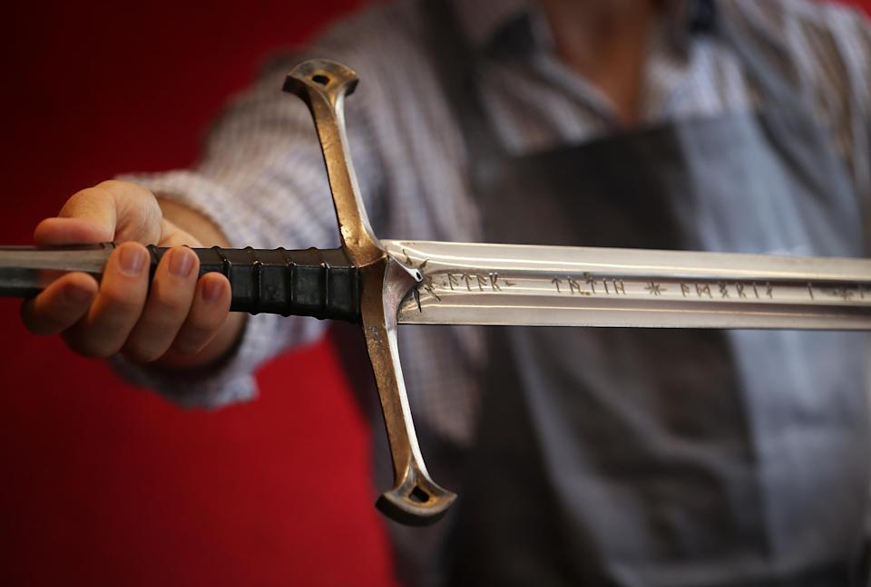 LONDON, ENGLAND - JULY 31:  A Bonhams employee holds 'Anduril' a prop sword belonging to Aragorn, hero of 'The Lord of the Rings' movie trilogy on July 31, 2014 in London, England. The sword, belonging to actor Sir Christopher Lee and estimated at $150,000-250,000, forms part of Bonhams 'There's No Place Like Hollywood' movie memorabilia auction taking place in New York on November 24, 2014.  (Photo by Peter Macdiarmid/Getty Images)