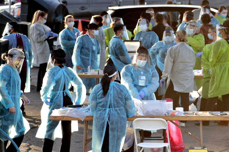FILE - In this June 27, 2020, file photo, medical personnel prepare to test hundreds of people lined up in vehicles in Phoenix's western neighborhood of Maryvale for free COVID-19 tests organized by Equality Health Foundation, which focuses on care in underserved communities. By early June, just a few weeks after man coronavirus-related restrictions were lifted, cases began spiking. Arizona has seen its cases quintuple from 13,000 on May 15 to 74,500 on Monday, and deaths from the virus have nearly doubled in the last six weeks. More than 1,500 people have died. (AP Photo/Matt York, File)