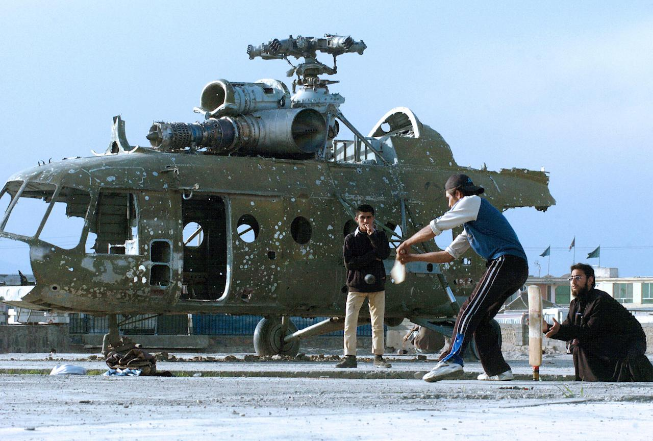 Kabul, AFGHANISTAN:  Afghan cricketers take part in a match on a patch of ground in front of a destroyed helicopter in Kabul,17 March 2006.   Cricket is popular among Afghans who have lived in Pakistan and recently returned to their country after decades of war.   AFP PHOTO/ SHAH Marai  (Photo credit should read SHAH MARAI/AFP/Getty Images)