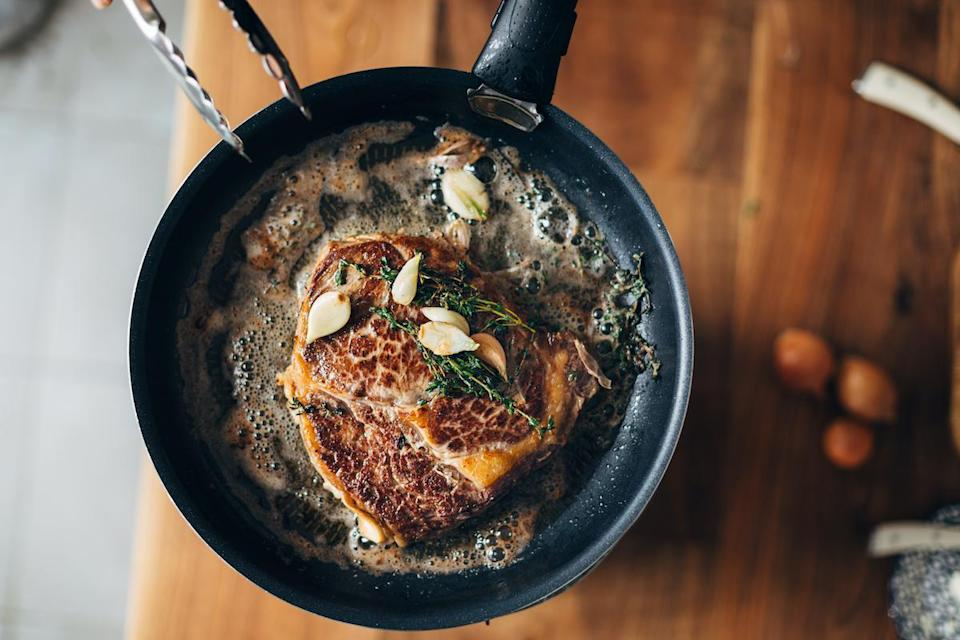 "<p>For maximum flavor, Shula's corporate chef and culinary director Demetrio Zavala first seasons steak with salt and pepper. He then waits for a pan to preheat over medium heat and, once it smokes lightly, he adds a teaspoon of canola oil and places the steak inside. He allows the steak to cook for two minutes on each side to reach medium-rare. Then, he adds butter, fresh thyme and whole garlic cloves to the pan. Spoon the butter from the pan over the steak. This is called basting, which adds moisture and flavor to the surface of the meat, Zavala says. If peeling garlic is a pain for you, here are <a href=""https://www.thedailymeal.com/cook/garlic-peeling-hack?referrer=yahoo&category=beauty_food&include_utm=1&utm_medium=referral&utm_source=yahoo&utm_campaign=feed"" rel=""nofollow noopener"" target=""_blank"" data-ylk=""slk:easy hacks from restaurant chefs"" class=""link rapid-noclick-resp"">easy hacks from restaurant chefs</a>.</p>"