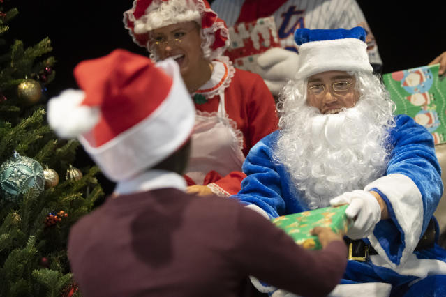 New York Mets outfielder Brandon Nimmo, right, dressed as Santa and his wife Chelsea Bradley as Mrs. Claus hand out gifts to local children during the team's annual Kids Holiday Party, Wednesday, Dec. 4, 2019, in New York. (AP Photo/Mary Altaffer)