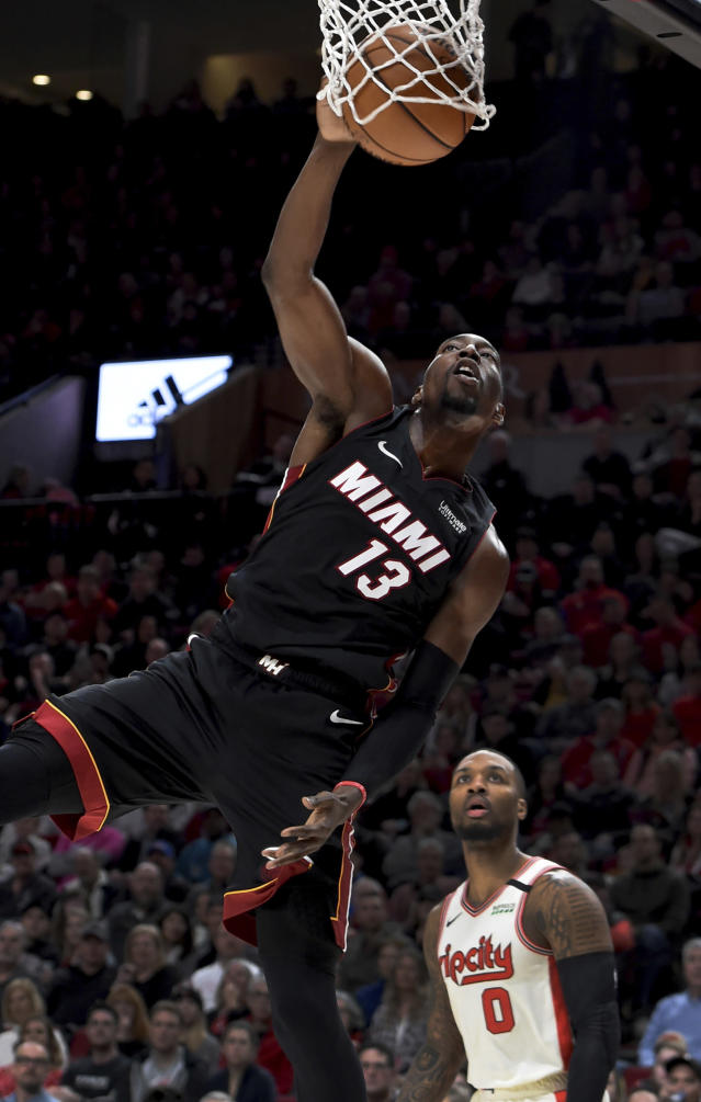 Miami Heat forward Bam Adebayo, left, dunks the ball as Portland Trail Blazers guard Damian Lillard, right, looks on during the first half of an NBA basketball game in Portland, Ore., Sunday , Feb. 9, 2020. (AP Photo/Steve Dykes)