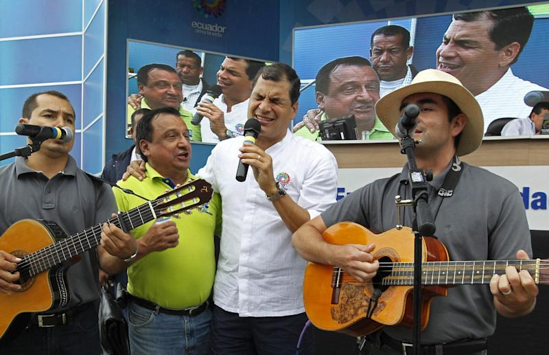 "Ecuador's President Rafael Correa, holding microphone, sings with a band and a supporter before the start of his his weekly broadcast ""Enlace Ciudadano,"" or ""Citizen Link"" in Manta, Ecuador, Saturday, June 29, 2013. While the Ecuadorean government appeared angry over U.S. threats of punishment if it accepts U.S. National Security Agency leaker Edward Snowden, there were also mixed signals about how eager it was to grant asylum. (AP Photo/Martin Mejia)"