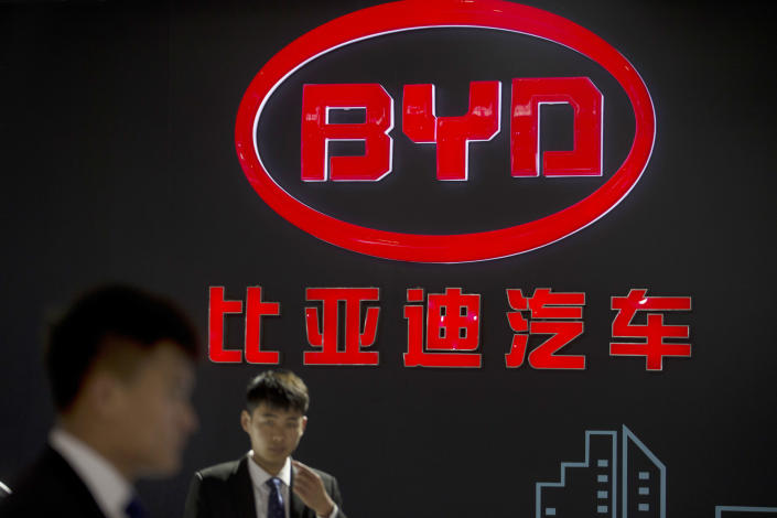 FILE - In this April 25, 2016, file photo, staff members stand near a logo for the BYD auto company as they wait for visitors at the Beijing International Automotive Exhibition in Beijing. The largest supplier of PPE to states this spring had never sold a single mask before the pandemic. But from mid-March to early June, Chinese electric vehicle maker BYD sold $930 million worth of masks and sanitizer to states. (AP Photo/Mark Schiefelbein, File)