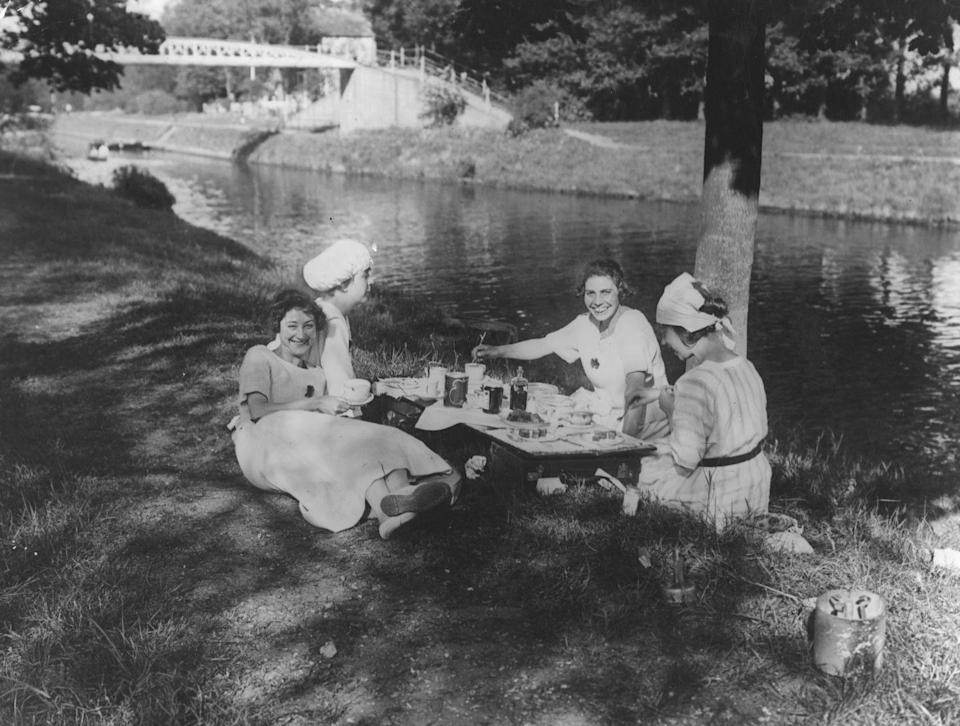 <p>A group of friends lounge in the shade as they enjoy a riverside picnic.</p>
