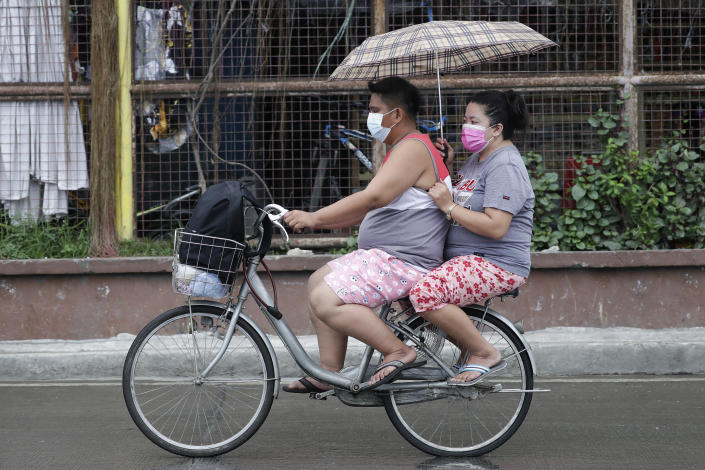 A couple uses an umbrella as they ride a bicycle through rain from Typhoon Vamco in Quezon city, Philippines on Wednesday, Nov. 11, 2020. Typhoon Vamco blew closer Wednesday to a northeastern Philippine region still struggling to recover from a powerful storm that left a trail of death and destruction just over a week ago, officials said, adding that thousands of villagers were being evacuated again to safety. (AP Photo/Aaron Favila)
