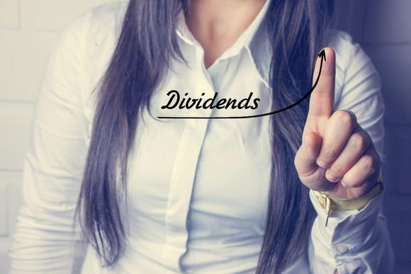 Woman pointing to the word dividends with an arrow beneath it curving up.
