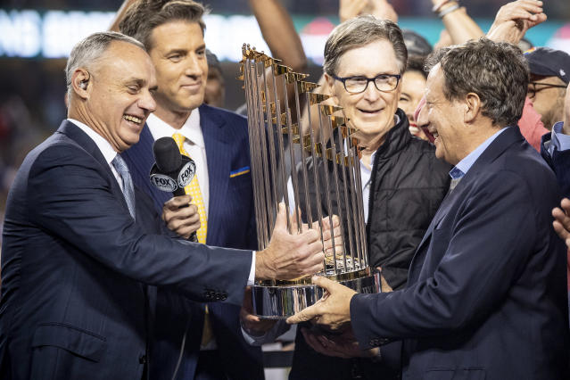 "Commissioner Rob Manfred (left) and Major League Baseball's owners, a group that includes billionaires such as <a class=""link rapid-noclick-resp"" href=""/mlb/teams/boston/"" data-ylk=""slk:Red Sox"">Red Sox</a> owner John Henry (second from right), are asking players to agree to a sliding scale of additional pay cuts on top of previously agreed upon prorated salaries. (Photo by Billie Weiss/Boston Red Sox/Getty Images)"