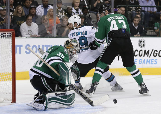 Dallas Stars goalie Dan Ellis (30) keeps focused on a loose puck as right wing Valeri Nichushkin (43) of Russia helps against pressure from San Jose Sharks center Joe Thornton (19) in the second period of an NHL hockey game, Thursday, Oct. 17, 2013, in Dallas. (AP Photo/Tony Gutierrez)
