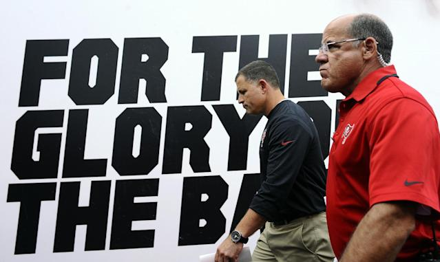 Tampa Bay Buccaneers head coach Greg Schiano, left, is escorted by a security guard off the field following the team's 33-14 loss to the San Francisco 49ers during an NFL football game Sunday, Dec. 15, 2013, in Tampa, Fla. (AP Photo/Brian Blanco)