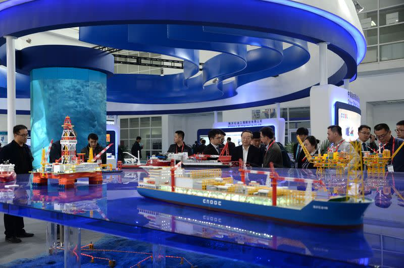 FILE PHOTO: Models of ships and offshore oil drilling equipment of China National Offshore Oil Co (CNOOC) are displayed in Beijing