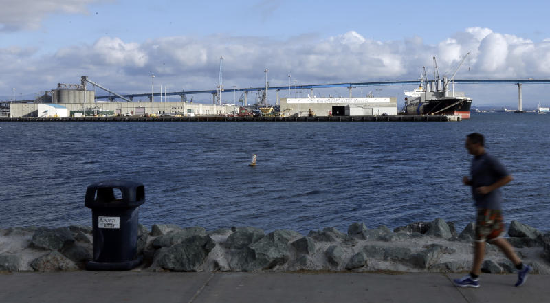 In this photo taken Oct. 10, 2012, a man runs on a path in front of the Tenth Avenue Marine Terminal in San Diego. The new media barons of San Diego, America's eighth-largest city, are upfront about wanting to use their newspaper to promote their agenda of downtown development and politically conservative causes — and they are making their points in a brash, bare-knuckle style. (AP Photo/Gregory Bull)