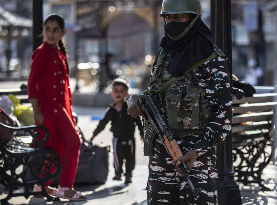 Kashmiri children play as an Indian paramilitary soldier keeps guard in Srinagar, Indian controlled Kashmir, Tuesday, Aug. 24, 2021. Indian government forces killed two senior rebel commanders and three other militants in two separate counterinsurgency operations in disputed Kashmir, police said Tuesday. (AP Photo/Mukhtar Khan)