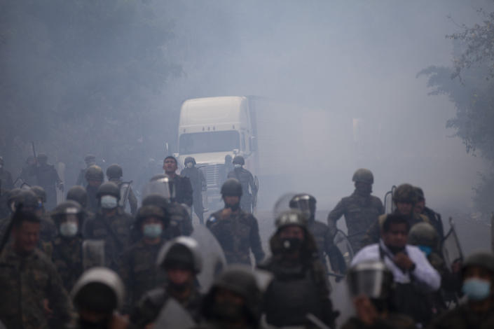 Guatemalan soldiers and police chase groups of migrants amid tear gas cloud at a roadblock on the highway in Vado Hondo, Guatemala, Monday, Jan. 18, 2021. The roadblock was strategically placed at a chokepoint on the two-lane highway flanked by a tall mountainside and a wall leaving the migrants with few options. (AP Photo/Sandra Sebastian)