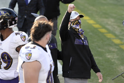 Baltimore Ravens head coach John Harbaugh celebrates after the Ravens beat the Tennessee Titans in an NFL wild-card playoff football game Sunday, Jan. 10, 2021, in Nashville, Tenn. (AP Photo/Mark Zaleski)