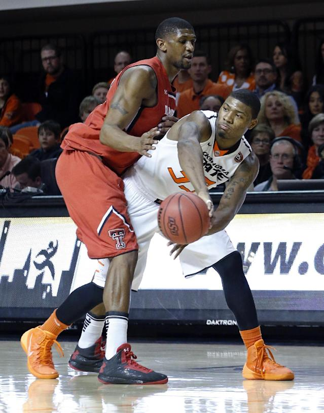 Oklahoma State guard Marcus Smart (33) passes off to a teammate in front of Texas Tech forward Jordan Tolbert (32) in the second half of an NCAA college basketball game in Stillwater, Okla., Saturday, Feb. 22, 2014. Oklahoma State won 84-62. (AP Photo/Sue Ogrocki)