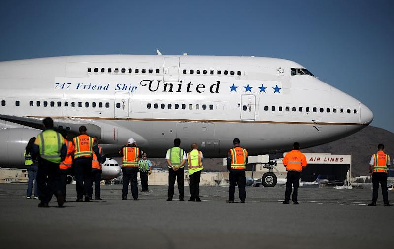Workers look on as United Airlines Flight 747 preapres to take off from San Francisco International Airport for its final flight to Honolulu, Hawaii -- one of the last before United retires its entire Boeing 747 fleet (AFP Photo/JUSTIN SULLIVAN)