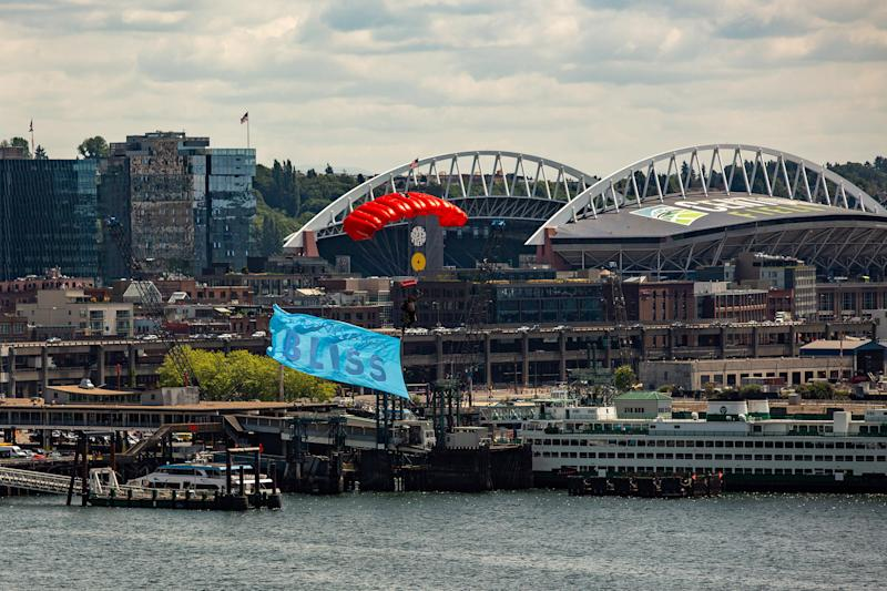 In celebration of Norwegian Bliss' christening, skydivers descend over the ship in Seattle, Washington