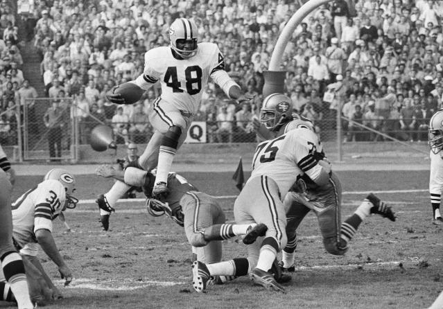 """File- This Nov. 2, 1970. file photo shows Green Bay Packer cornerback Ken Ellis (48) leaping as he returns a 49er punt in third quarter NFL action in San Francisco. Packer guard at right is Forrest Gregg (75). """"It's going to be a long time, another 100 years, before somebody wins himself six titles,"""" said Herb Adderley, the Hall of Fame cornerback for Vince Lombardis great Green Bay Packers teams of the 1960s. Adderley, who turns 80 next month, won five championships in Green Bay, including the first two Super Bowls, plus another with Tom Landrys Dallas Cowboys in 1971, as did Forrest Gregg, who died last month at age 85. (AP Photo/File)"""