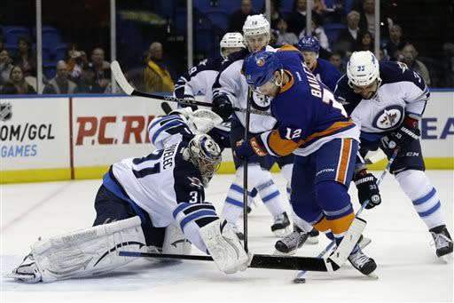 Winnipeg Jets goalie Ondrej Pavelec (31) of Czech Republic makes a save with New York Islanders center Josh Bailey (12) in front of the crease in the second period of their NHL hockey game at Nassau Coliseum in Uniondale, N.Y., Tuesday, April 2, 2013. Bailey scored near the end if the second period. (AP Photo/Kathy Willens)