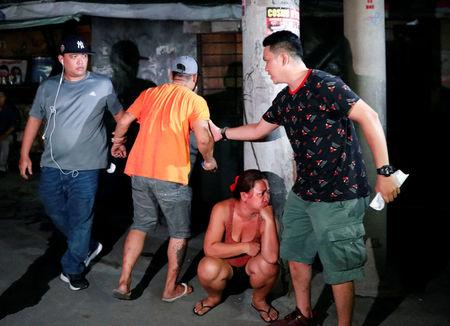 Plainclothes police officer hold a man as they comfort him after his brother, who police say was killed in a spate of drug-related violence overnight, was shot to death in Manila, Philippines August 16, 2017.  REUTERS/Dondi Tawatao