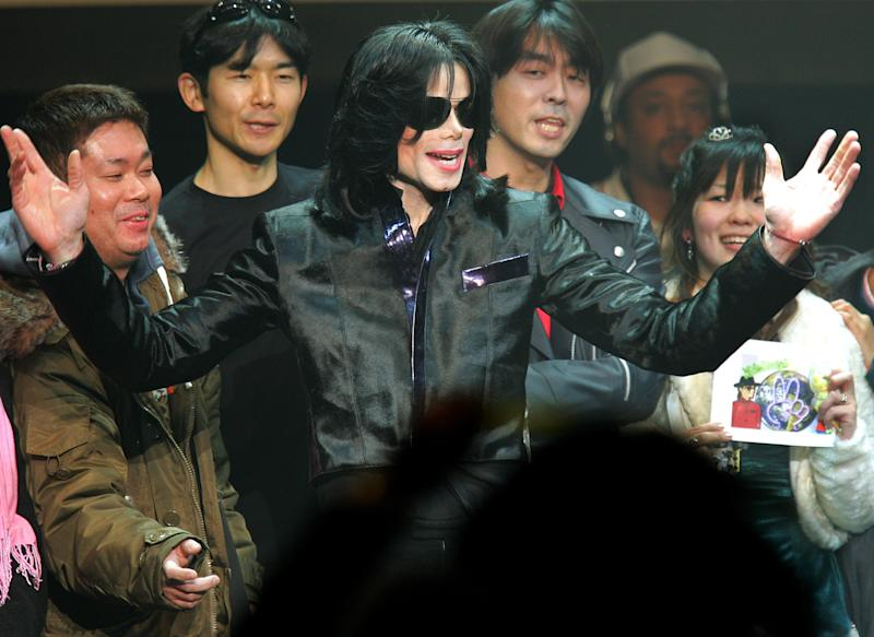 """FILE - In this March 9, 2007 file photo, U.S. pop singer Michael Jackson greets his fans during an event """"Fan Appreciation Day"""" in Tokyo. Michael Jackson's estate is suing a man and three companies in Japan, alleging they are using the name and likeness of the late pop star on key chains, mugs and other products without permission. The lawsuit filed in Tokyo District Court last month, Sept. 2013, does not seek money but demands the actions stop. It names Ryosuke Matsuura and three companies, Michael Jackson Asian Rights, Michael Jackson Enterprises and Michael Jackson World. (AP Photo/Itsuo Inouye, File)"""