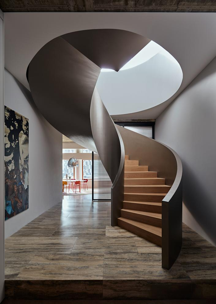 """<div class=""""caption""""> The Powerhouse Company signature spiral staircase connects the top floor of the existing building with the newly created penthouse. The stair is made of champagne-colored stucco and oak steps. </div>"""