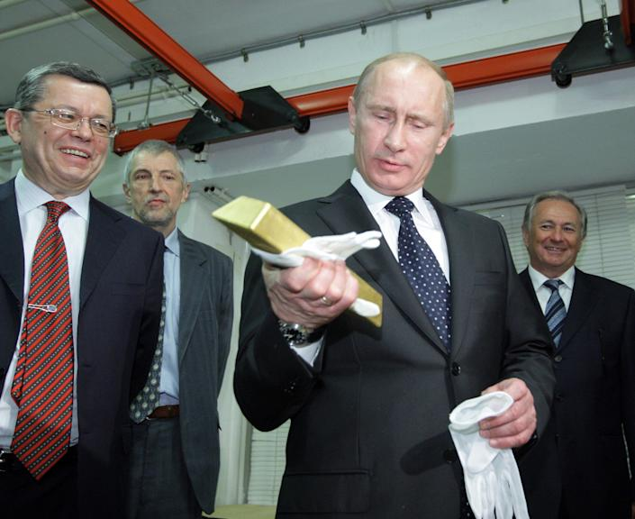 Vladimir Putin (C) holds a gold bar while visiting the Central Depository of the Bank of Russia on January 24, 2011 in Moscow. (Photo credit should read Alexsey Druginyn/AFP/Getty Images)