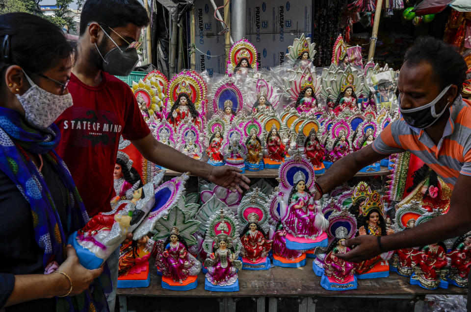 People buy clay idols of Laxmi, the Hindu goddess of wealth, ahead of Laxmi Puja festival in Kolkata, India, Thursday, Oct. 29, 2020. India's confirmed coronavirus caseload surpassed 8 million on Thursday with daily infections dipping to the lowest level this week, as concerns grew over a major Hindu festival season and winter setting in. (AP Photo/Bikas Das)