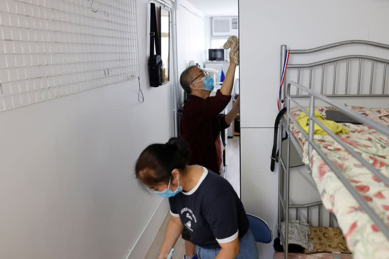Lau Kai Fai, 70, clean his new home in a four-story building made from pre-fabricated parts with his wife at Shek Kip Mei, in Hong Kong