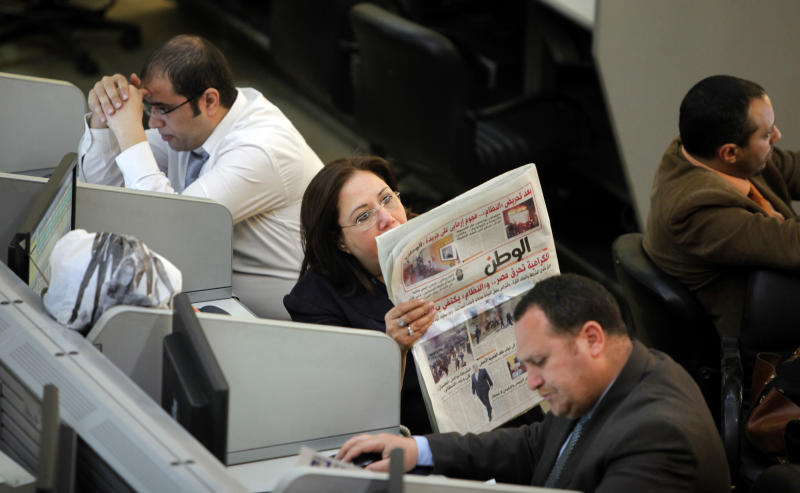 "An Egyptian trader reads a newspaper at the stock market in Cairo, Egypt, Saturday, March 10, 2013. Egypt is trying to meet conditions to close on a $4.8 billion loan package from the International Monetary Fund and an agreement would unlock more of the $1 billion in U.S. assistance promised by President Barack Obama last year. Arabic headline reads, ""hate is burning Egypt."" (AP Photo/Amr Nabil)"