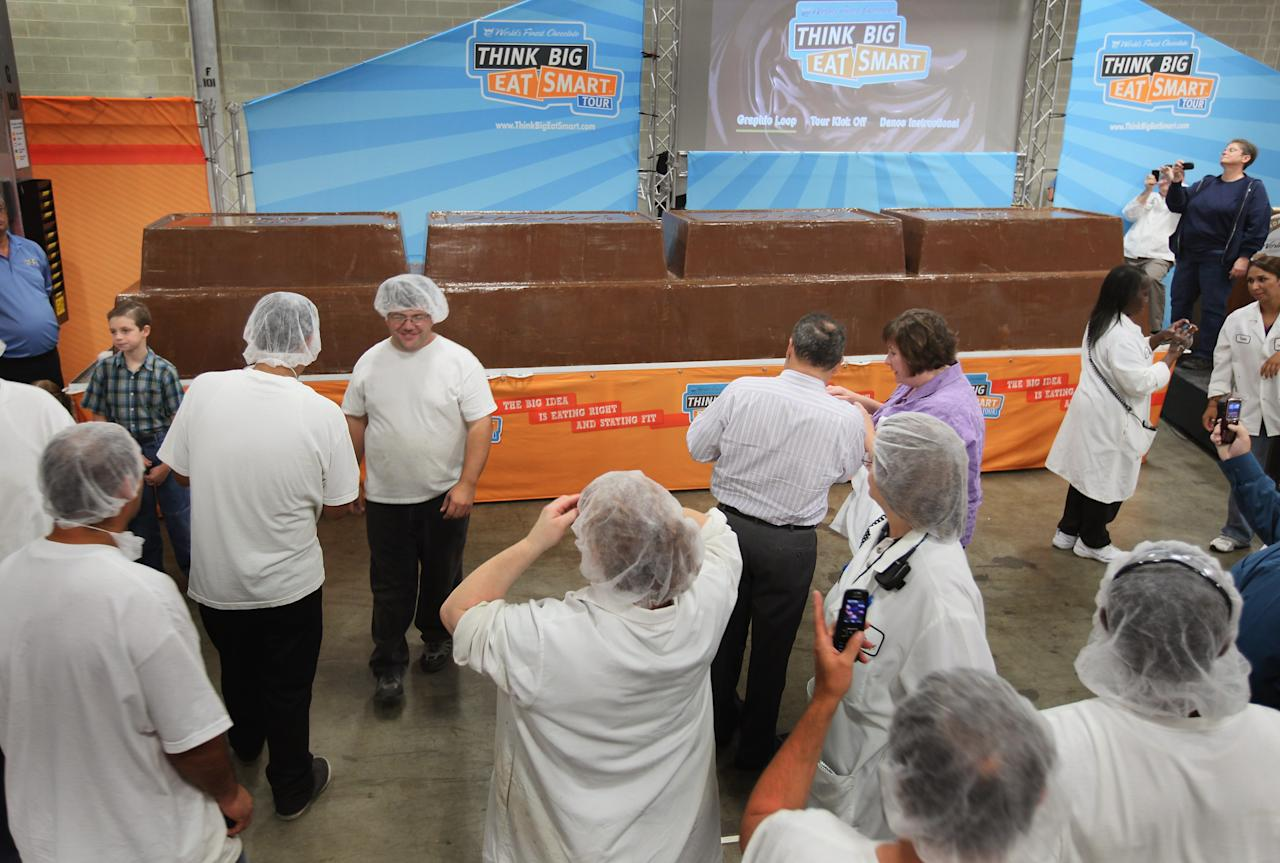 CHICAGO, IL - SEPTEMBER 13:  Workers at the World's Finest Chocolate company look at a 12,290 pound chocolate bar they created to set a new Guinness World Record September 13, 2011 in Chicago, Illinois. The bar, which stands nearly 3 feet high and measures 21 feet long, beat the previous record chocolate bar by more than a ton.  (Photo by Scott Olson/Getty Images)